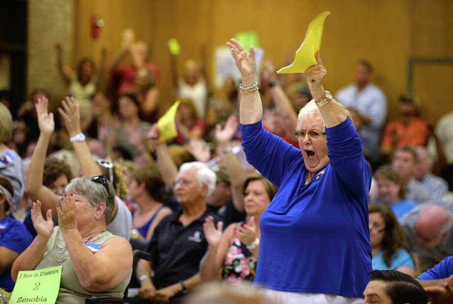 Dottie Caruth cheers after Fred Shafer TEA monitor points finger to trusties for financial crisis and declares that he will not back board's decision. More than 250 people attended Monday nights Beaumont Independent School District's board meeting with signs and banners showing dissent for trusties and a $25 million shortcoming in the 2014-2015 budget.  Photo taken Monday, June 30, 2014 Guiseppe Barranco/@spotnewsshooter Photo: Guiseppe Barranco, Photo Editor
