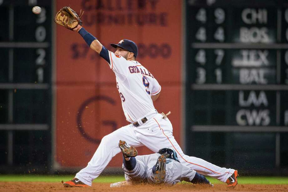 Try as he might, Astros shortstop Marwin Gonzalez couldn't get to a throw from catcher Jason Castro before Seattle's James Jones reaches second base on a steal attempt in Monday's 10-4 win for the Mariners at Minute Maid Park. Photo: Smiley N. Pool / © 2014  Smiley N. Pool
