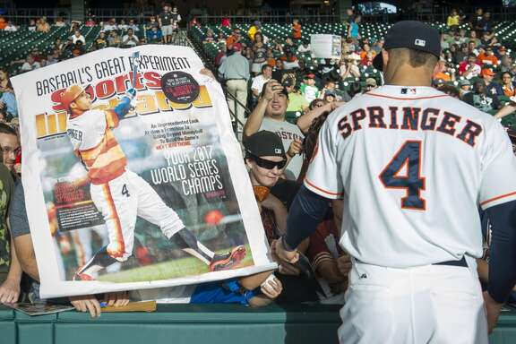 A Houston Astros fan holds up a large print of the Sports Illustrated cover featuring right fielder George Springer as he signs autographs before a game against the Seattle Mariners.