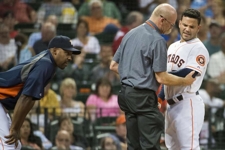Astros second baseman Jose Altuve  is checked by assistant athletic  trainer Rex Jones and manager Bo Porter after being hit by a pitch. Photo: Smiley N. Pool, Houston Chronicle