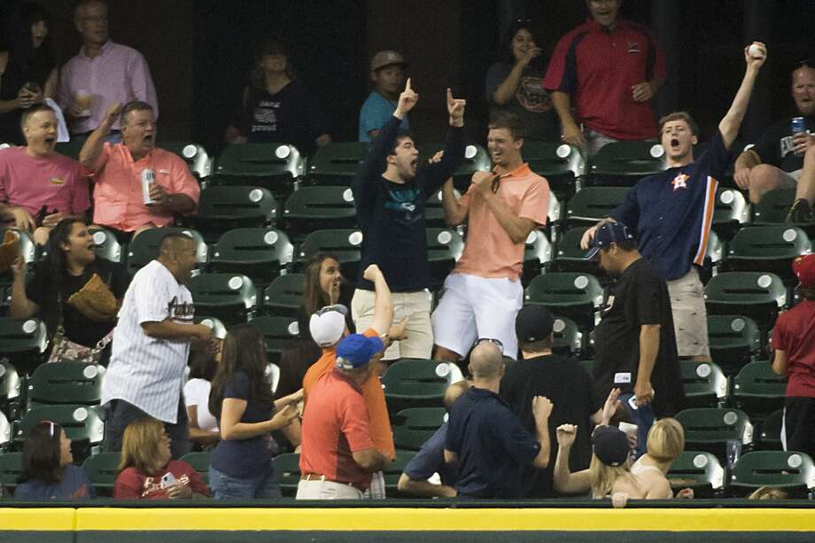 A Houston Astros fan in the Crawford Boxes tosses back a home run ball off the bat of Mariners second baseman Robinson Cano during the seventh inning. Photo: Smiley N. Pool, Houston Chronicle