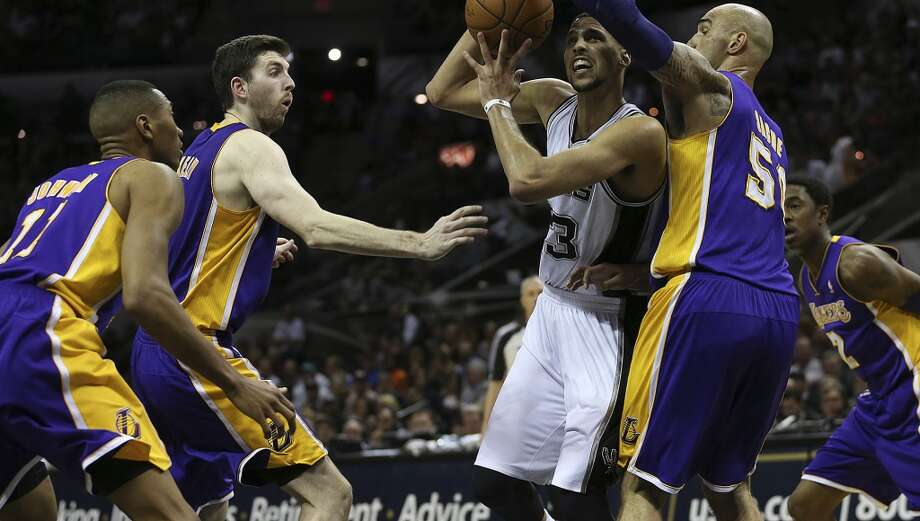 San Antonio Spurs' Austin Daye goes between the defense of, from left, Los Angeles Lakers' Wesley Johnson, Ryan Kelly and Robert Sacre during the second half at the AT&T Center, Wednesday, April 16, 2014. The Lakers won 113-100. Photo: Jerry Lara, San Antonio Express-News