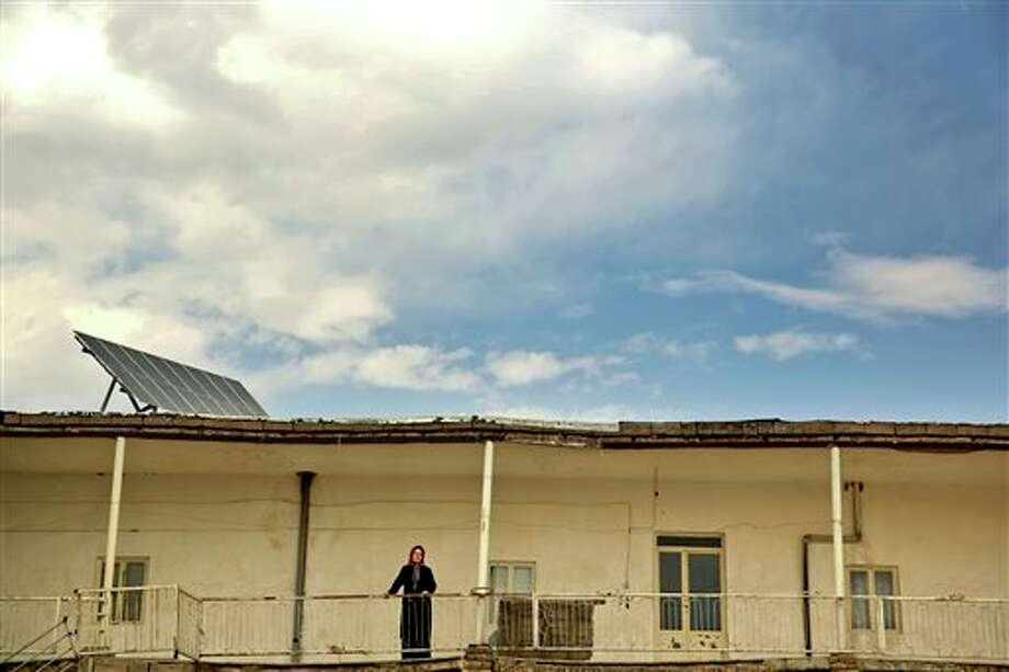 In this June, 22, 2014 photo, a woman stands on the balcony of her home powered by solar panels in Sichanloo, a hamlet 200 kilometers (125 miles) northwest of the capital, Tehran, Iran. In this village nestled in the arid hills of rural Iran, the government-subsidized solar panels on the rooftops of homes here provide both needed electricity and a shining symbol of efforts by the Islamic Republic to wean itself off fossil fuels and nuclear power. (AP Photo/Ebrahim Noroozi) Photo: Ebrahim Noroozi, AP / AP