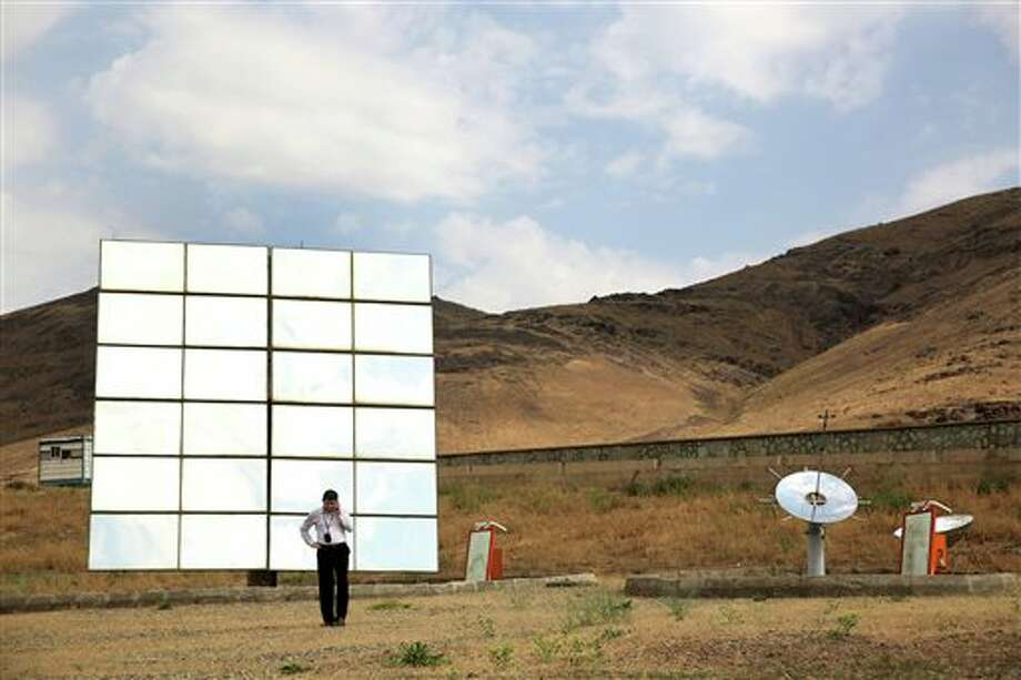 In this June, 22, 2014 photo, an Iranian student speaks on his phone as he and others tour the Taleghan Renewable Energy Site in Taleghan,160 kilometers (99 miles) northwest of capital Tehran, Iran. Solar has been a hot topic of discussion in Iran, which this year fielded a team of university students to compete in a U.S. solar car contest in July. Saman Mirhadi, a senior government official, said the government installed solar panels at some 1,000 locations across Iran, including the rooftops of mosques, schools and government buildings. (AP Photo/Ebrahim Noroozi) Photo: Ebrahim Noroozi, AP / AP