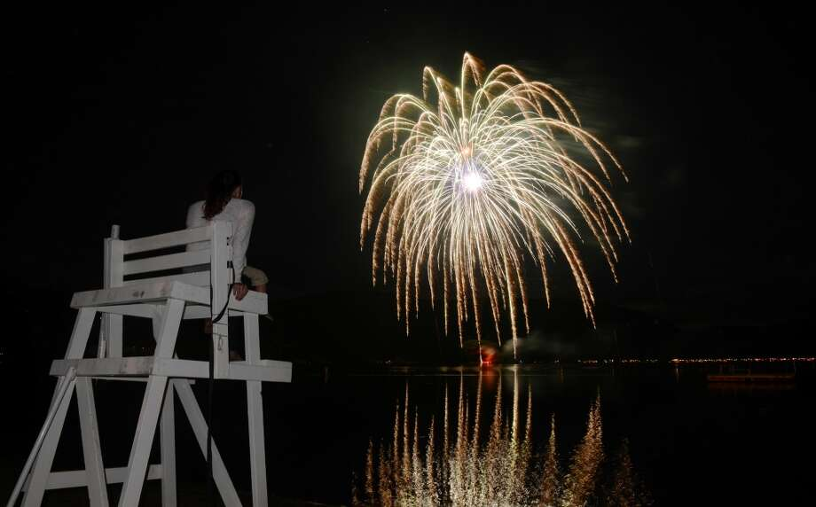 Andrea LaRosa, of Danbury, watches the Independence Day fireworks display from atop the lifeguard's chair at Candlewood Town Park on Candlewood Lake in Danbury, Conn. Saturday, June 28, 2014. Photo: Tyler Sizemore