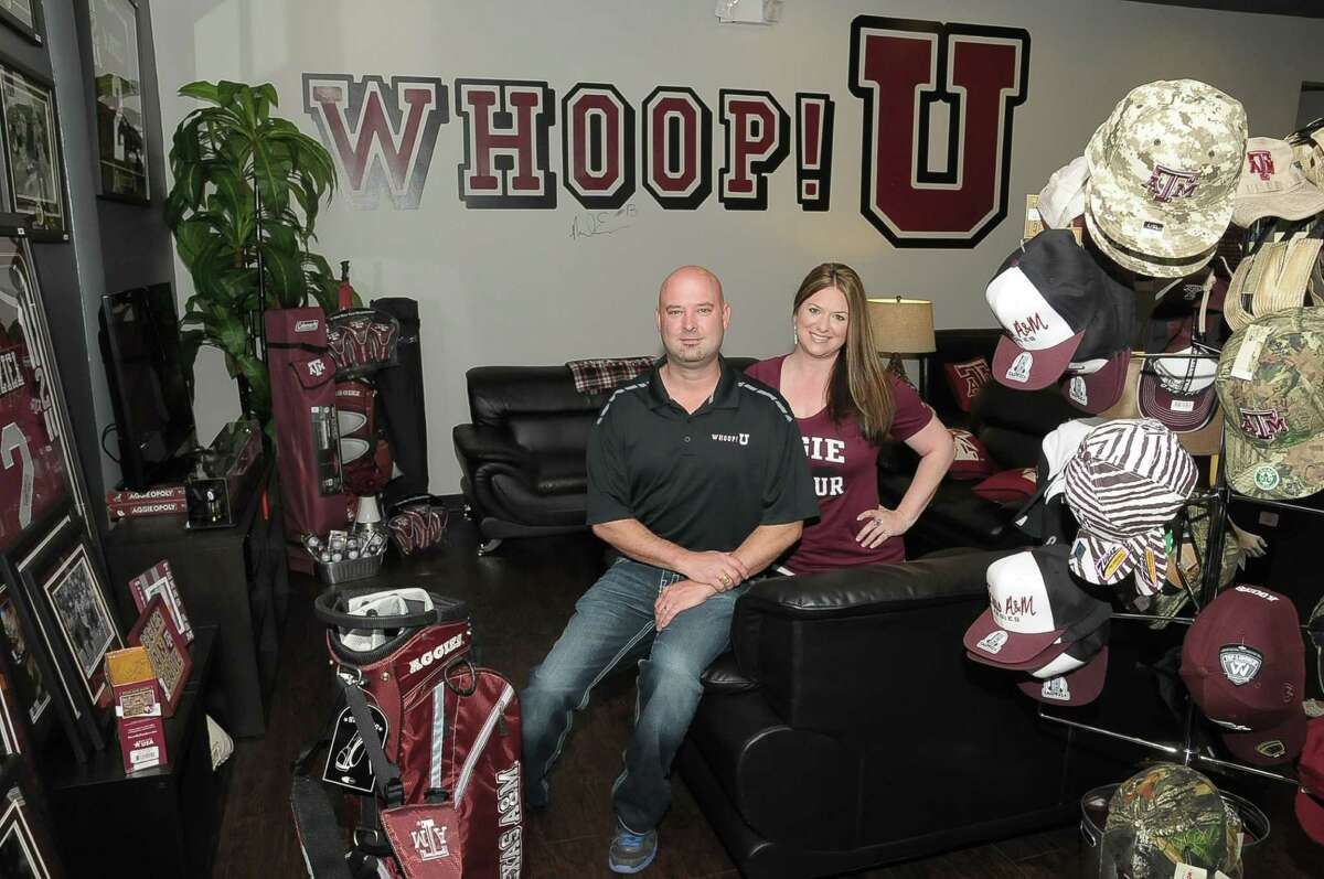 Nathan Leonard and Stacy Leonard display some merchandise at their Whoop U store in Cypress, which specializes in Texas A&M merchandise.