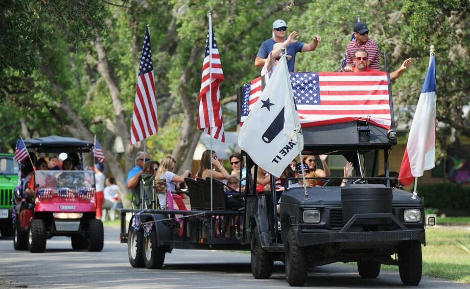 Participants in the 2013 Hollywood Park Fourth of July parade wave at residents lining the streets. The parade and picnic, held by the town's homeowners association, is one of several Independence Day celebrations in the area. Photo: File / Stone Oak Weekly