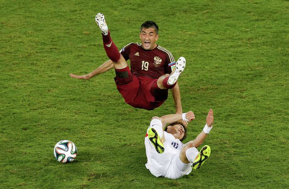 South Korea's Ki Sung-yueng, bottom, fouls Russia's Alexander Samedov during the group H World Cup soccer match between Russia and South Korea at the Arena Pantanal in Cuiaba, Brazil, Tuesday, June 17, 2014. Photo: Thanassis Stavrakis, ASSOCIATED PRESS / AP2014