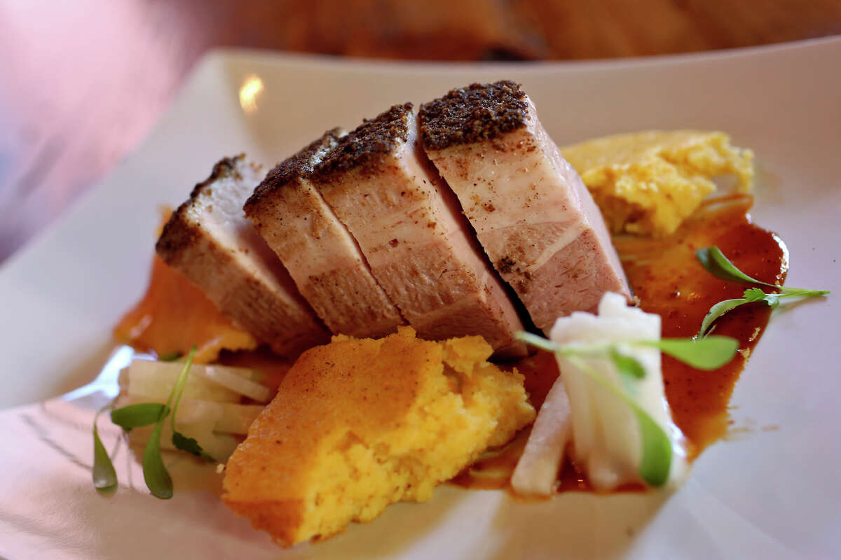 In a more inventive dish, pork belly is seasoned with a coriander/cumin rub, salsa negra, jicama and cilantro and served with masa spoon bread at The Granary in San Antonio.
