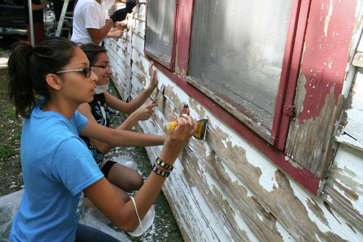 Go Youth members and Davis High School students Disela Hinojosa and Daniela Melandez spend a Saturday morning scraping old paint to get Jose and Dolores Davalos' home ready to repaint.