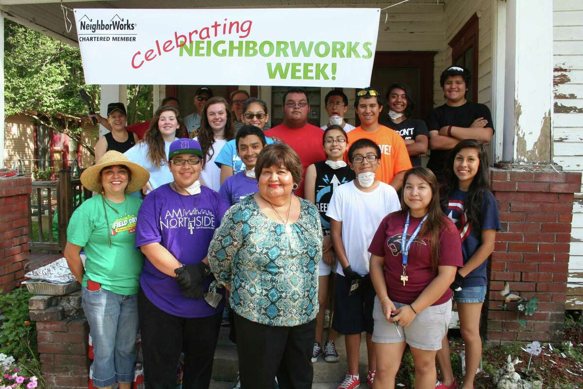 Students from the GoYouth group and neighbors from the Near Northside community painted the outside of the home of Dolores Davalos, center, and her husband Jose.
