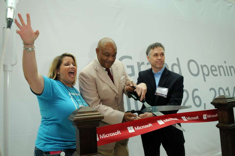 Sabrina Dziubarczyk, Mall Microsoft Retail Store Manager, from left, championship boxer George Foreman, and Lane Sorgen, Microsoft General Manager for South Central US, cut the ceremonial ribbon during the Microsoft Retail Store Opening event in The Woodlands Mall on Thursday. Photo: Jerry Baker, Freelance
