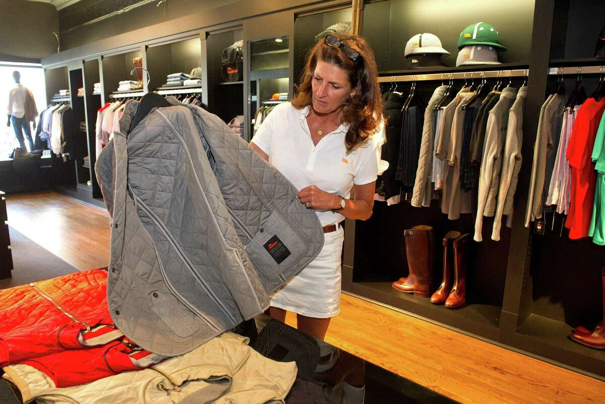 Store manager Leslie Shantz shows the craftmanship in the inside of a jacket at the newly opened Casablanca store on Greenwich Avenue in Greenwich, Conn., on Tuesday, July 1, 2014. The store sells equipment for polo players, including helmets, boots, and mallets, as well as luxury clothing.