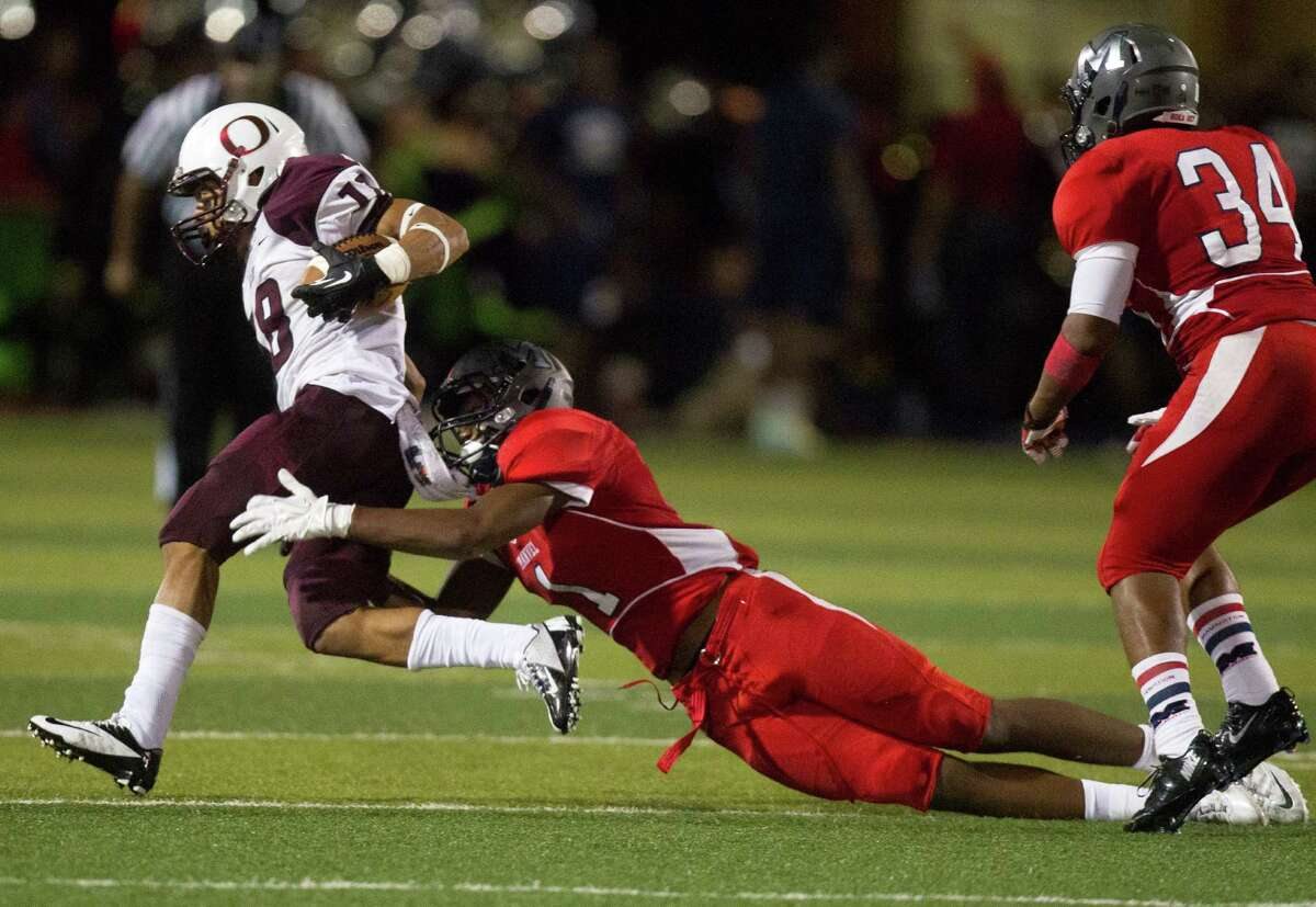 Pearland wide receiver Jacoby Lewis (18) is brought down by Manvel defensive back Deontay Anderson during the second half of a high school football game at Alvin Memorial Stadium on Friday, Nov. 1, 2013, in Alvin ( J. Patric Schneider / For the Chronicle )