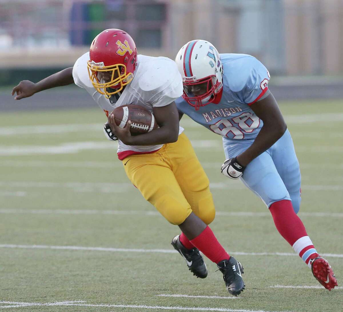 9/13//13: Yates' Bruce Wilson #42 escapes the tackle of Madison's Nnanna Ezenwa on September 13, 2013 at Butler Stadium in Houston, Texas.