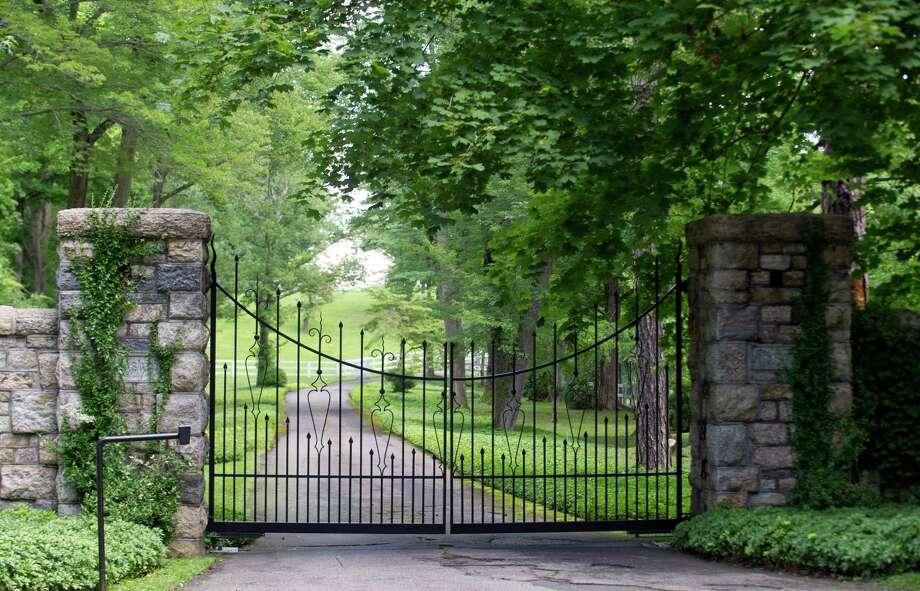 The gated home of Raj Rajaratnam at 577 Round Hill Road in Greenwich, Conn., appears in this file photo. Rajaratnam's driver sued him in federal court in New Haven on Friday. Photo: Lindsay Perry / Stamford Advocate