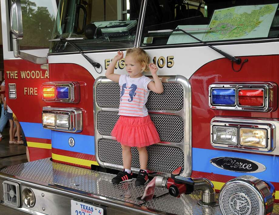 David Ong shows his daughter, Mary Kenneth, the fire hoses on the back od a fire engine during the Good Neighbor Day event at The Woodlands Fire Department Station #5,10100 Branch Crossing Drive. Children were able to meet firefighters, try on their gear, learn about the fire equipment and fire safety during the event. Photograph by David Hopper Photo: David Hopper, For The Chronicle / freelance
