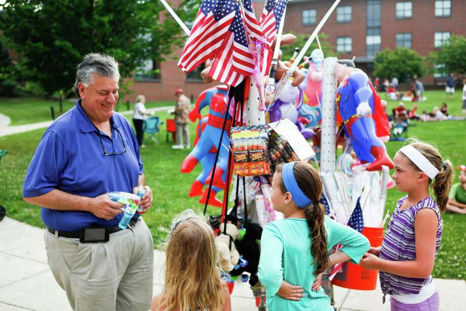 A vendor shares a laugh with a group of girls during last year's Fourth of July celebration at Darien High School. Cameron Lancaster / For the Darien News Photo: Contributed Photo / Darien News