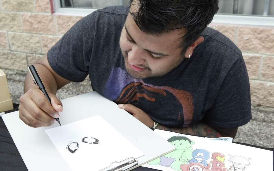 Local cartoonist Marcus Rocco sketches outside of Collectors Authority on Southeast Military Drive recently. Photo: Cynthia Esparza / For The Express-News / For the San Antonio Express-News