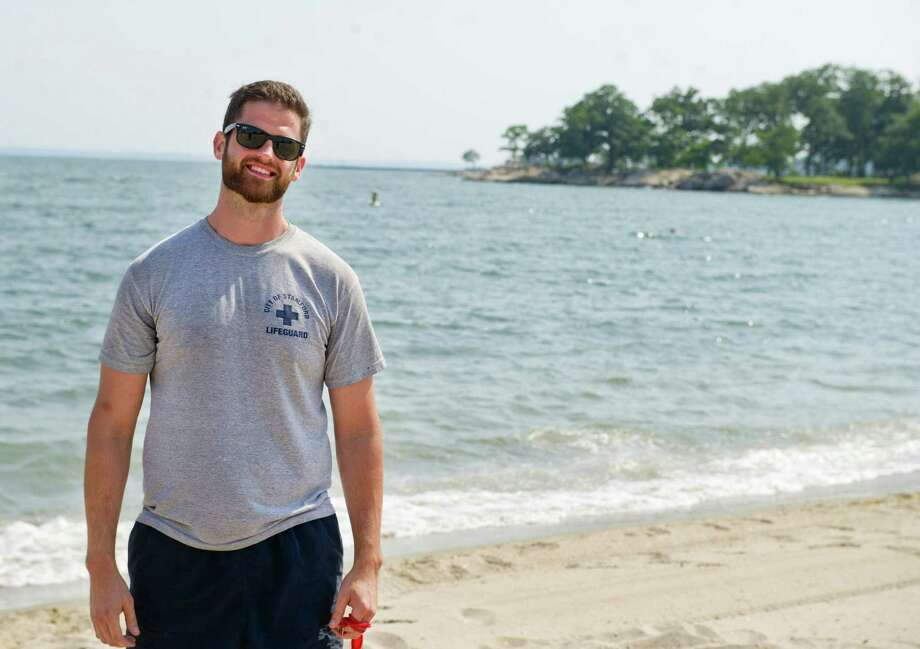 Dave Flynn stands on Cove Island Beach on Tuesday, July 1, 2014. Behind Flynn is a rocky area where a swimmer jumped in Monday but struggled to reach the shore. Flynn rescued the swimmer using a kayak. Photo: Lindsay Perry / Stamford Advocate