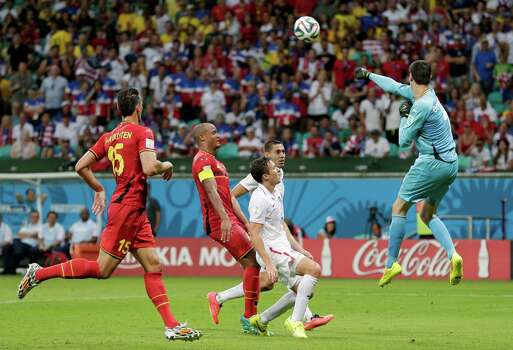 Belgium's goalkeeper Thibaut Courtois clears the ball over United States' Matt Besler and Clint Dempsey during the World Cup round of 16 soccer match between Belgium and the USA at the Arena Fonte Nova in Salvador, Brazil, Tuesday, July 1, 2014. (AP Photo/Marcio Jose Sanchez) Photo: Marcio Jose Sanchez, Associated Press / AP