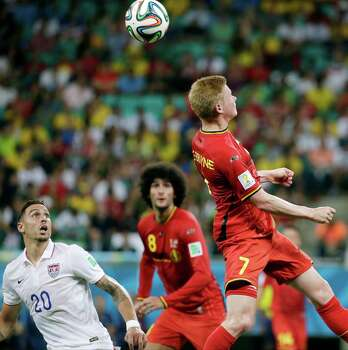 Belgium's Kevin De Bruyne (7) goes for a header as United States' Geoff Cameron (20) looks on during the World Cup round of 16 soccer match at the Arena Fonte Nova in Salvador, Brazil, Tuesday, July 1, 2014. At left is United States' Geoff Cameron. Center Belgium's Marouane Fellaini.(AP Photo/Felipe Dana) Photo: Felipe Dana, Associated Press / AP