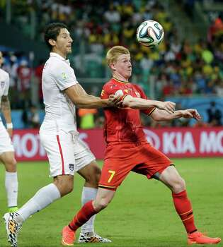 Belgium's Kevin De Bruyne, right, and United States' Omar Gonzalez, left, fight for the ball during the World Cup round of 16 soccer match between Belgium and the USA at the Arena Fonte Nova in Salvador, Brazil, Tuesday, July 1, 2014. (AP Photo/Felipe Dana) Photo: Felipe Dana, Associated Press / AP