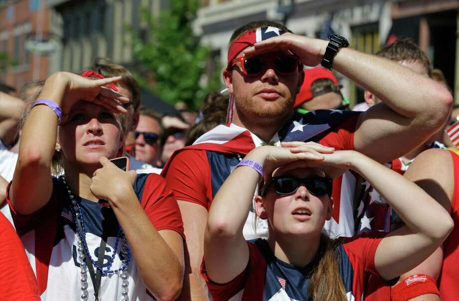 United States fans shade their eyes as they watch a big-screen television during the World Cup soccer match between the United States and Belgium at a viewing party in Indianapolis, Tuesday, July 1, 2014. (AP Photo/Michael Conroy) Photo: Michael Conroy, Associated Press / AP