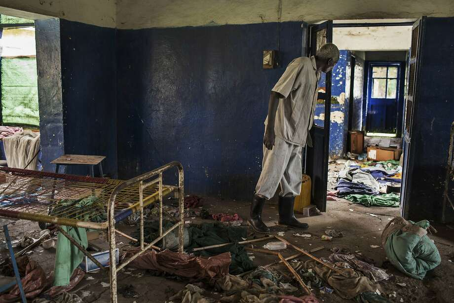 An unidentified man searches through the rubble of a hospital tuberculosis ward after many patients were slain in their beds in the city of Malakal. Photo: Matthew Abbort, Associated Press
