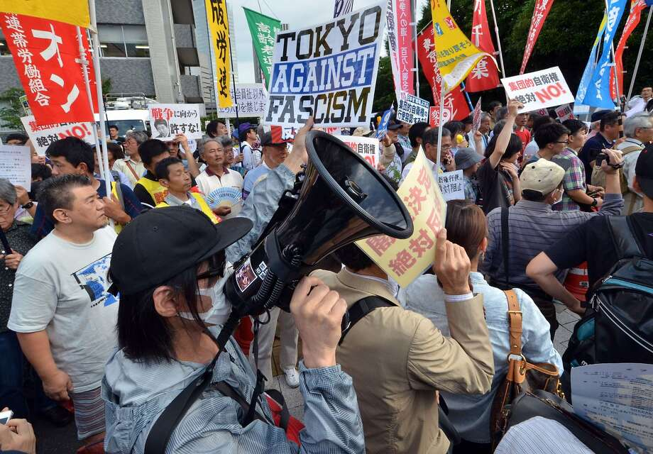 "Protestors hold placards and shout anti Abe government slogans during a rally in front of the prime minister's official residence in Tokyo on July 1, 2014. Japan loosened restrictions on its powerful military, allowing it to go into battle in defence of allies, in a major and highly controversial shift for the nation's pacifist stance. Prime Minister Shinzo Abe told a press conference: ""No matter what the circumstances, I will protect Japanese people's lives and peaceful existence. As the prime minister, I have this grave responsibility. With this determination, the cabinet approved the basic policy for national security.""  AFP PHOTO / Yoshikazu TSUNOYOSHIKAZU TSUNO/AFP/Getty Images Photo: Yoshikazu Tsuno, AFP/Getty Images"