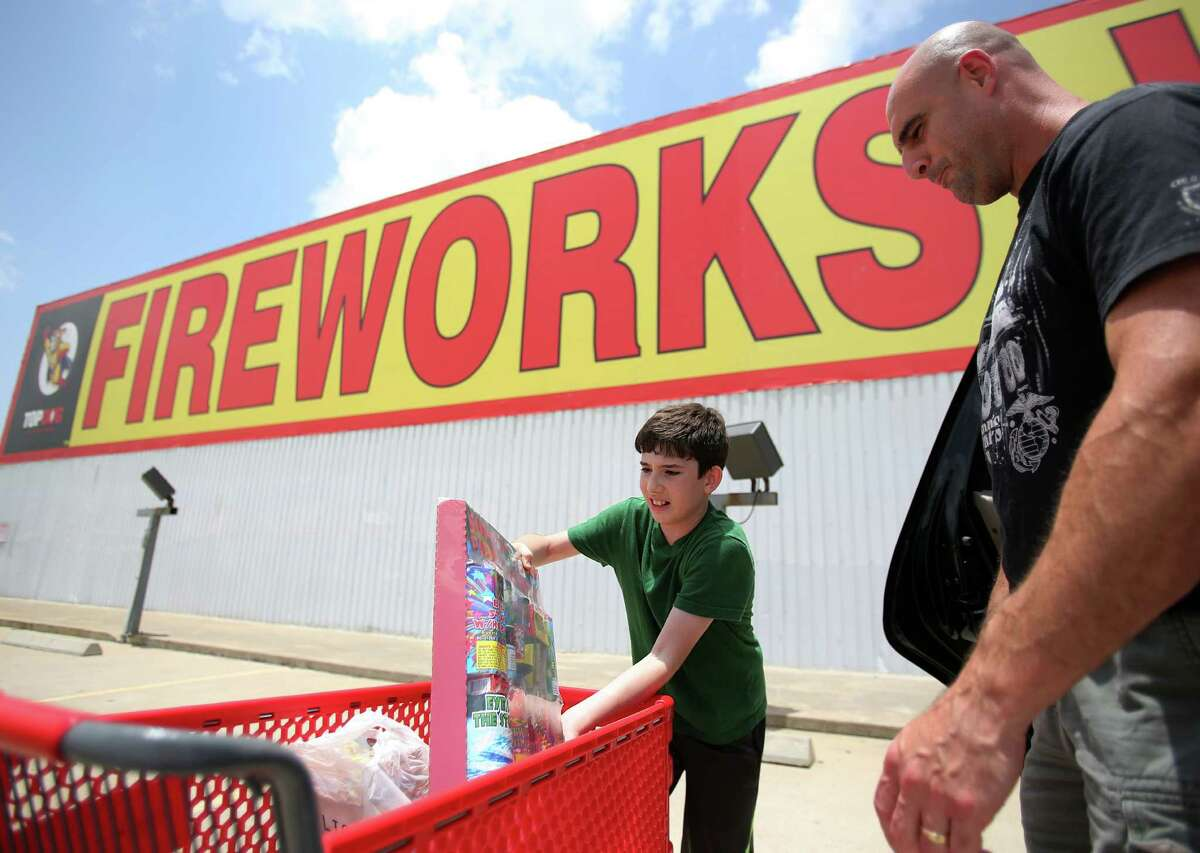 Noah Zakharia, 10, happily helps his father Jack Zakharia load the fireworks into their vehicle after shopping at Top Dog Fireworks on July 1, 2014, in Houston, Tx.