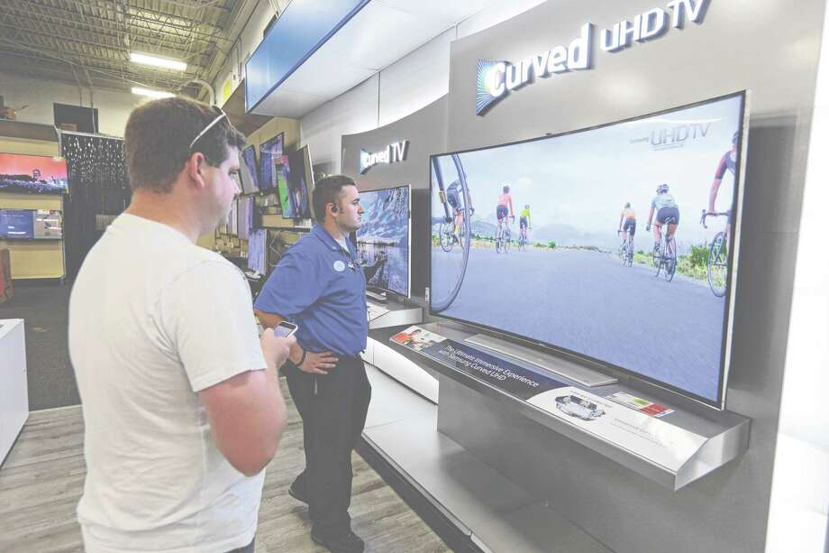 In this Wednesday, June 18, 2014 photo, Jake Willis, center, home theatre supervisor at the Best Buy store in Greenwood, Ind., talks with customer Landon Leichter, of Spencer, Ind., at a display featuring a Samsung 78-inch curved television on display at the store in Greenwood, Ind. The 78-inch television is flanked by 65-inch versions. Americans increasingly are replacing their once-enviable 50-inch TVs with even bigger screens. (AP Photo/Michael Conroy) ORG XMIT: INMC203 Photo: Michael Conroy / AP