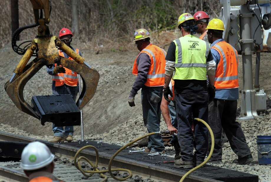 Crews are working Wednesday, May 7, 2014, to repair the railroad crossings on the Danbury branch of the Metro-North line. Photo: Carol Kaliff / The News-Times