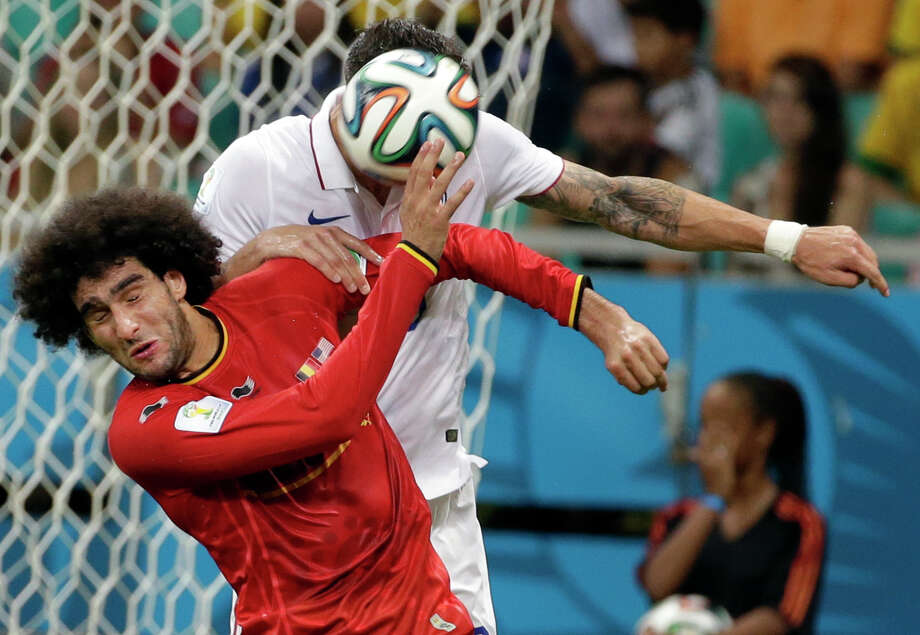 Belgium's Marouane Fellaini, front left, goes for a header with United States' Geoff Cameron, back, during the World Cup round of 16 soccer match between Belgium and the USA at the Arena Fonte Nova in Salvador, Brazil, Tuesday, July 1, 2014. (AP Photo/Felipe Dana) Photo: Felipe Dana, Associated Press / AP