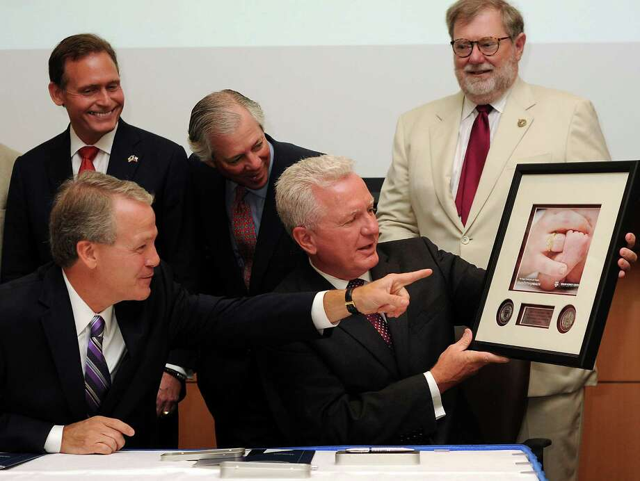 Houston Methodist's Marc Boom, left, and Texas A&M's Brett Giroir look at a gift given after Tuesday's partnership announcement. Also pictured in the back, from left, are state Rep. John Zerwas, Robert Robbins and Charles Schwartz. Photo: Dave Rossman, Freelance / © 2014 Dave Rossman