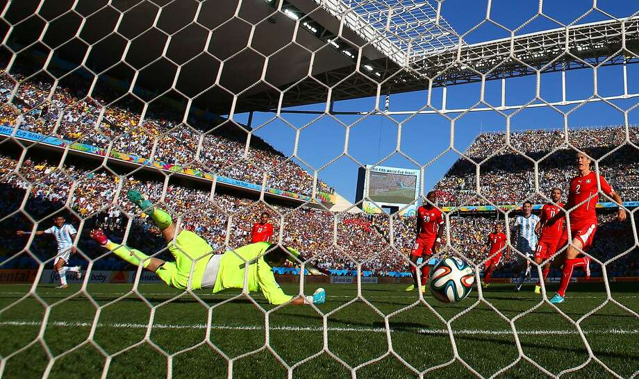 Angel Di Maria slots his shot past Diego Benaglio, Switzerland's goalkeeper, to send Argentina to the quarterfinals. Photo: Ronald Martinez, Getty Images