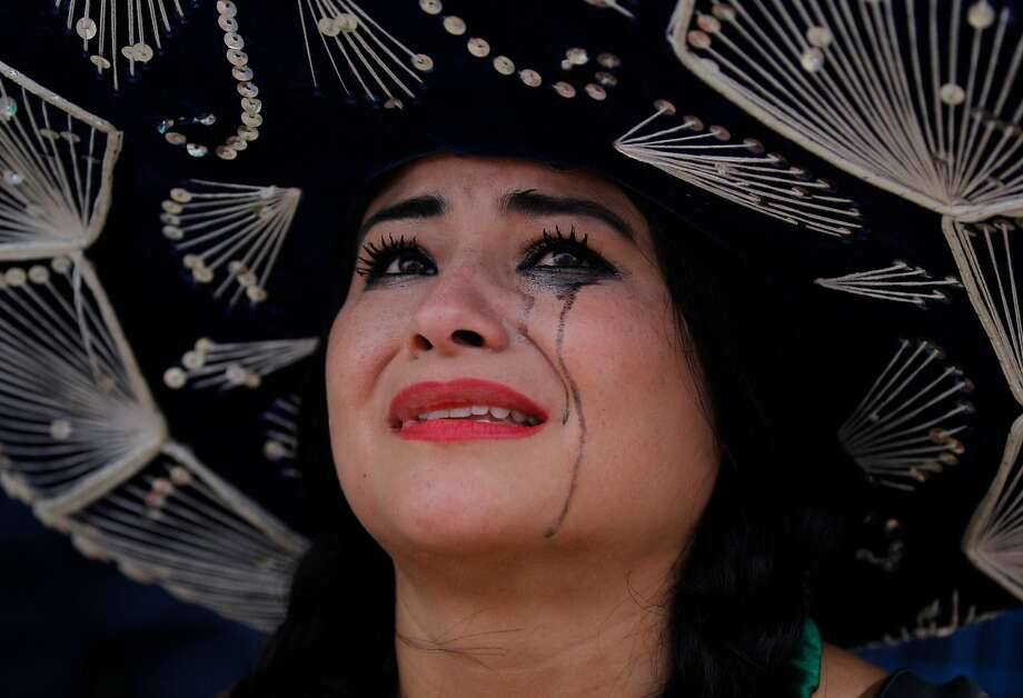 Tears under the sombrero: A Mexico fan cries after her team fell to the Netherlands in a World 