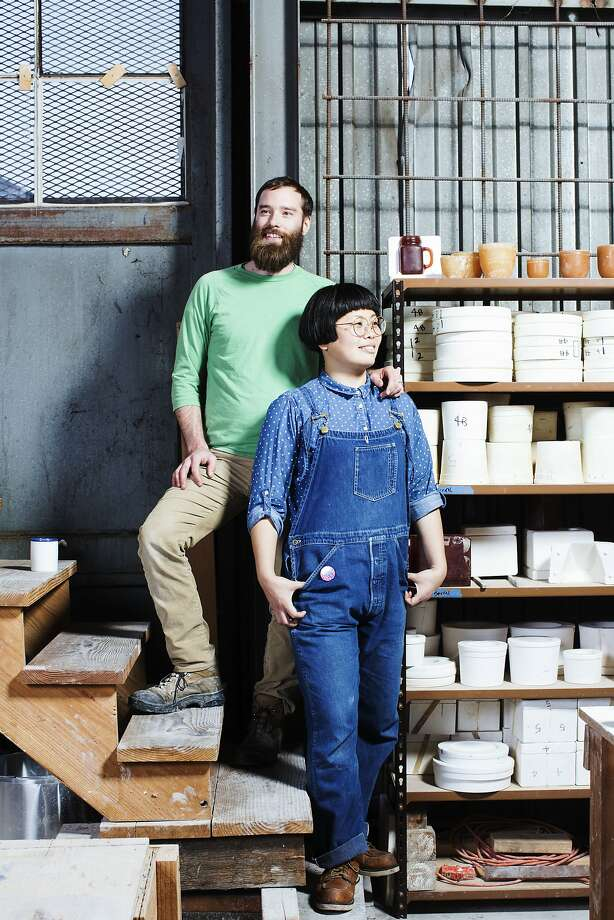 Ceramic artists Jay and Rie Dion of Atelier Dion strike a pose at their studio in Oakland. Photo: Stephen Lam, Special To The Chronicle