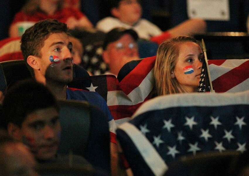 The mood of soccer fans Megan Jeffries (right) and Taylor Cowart turn somber as Belgium scores a goal on the United States team during a watch party at the Palladium Theaters on Tuesday, July 1, 2014. Initially loud and raucous chants and cheers for the team by the supporters were eventually stifled as Belgium managed a 2-1 victory over the United States in World Cup competition.