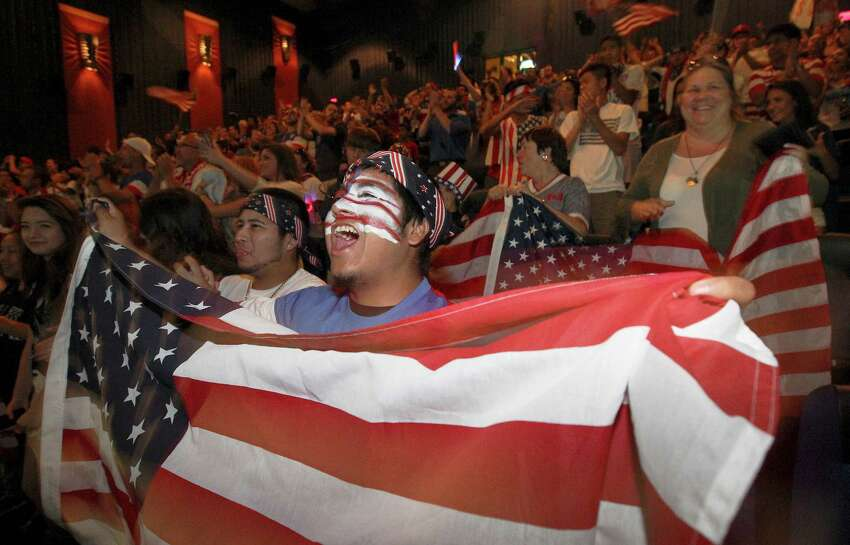 Rudy Rosales waves the U.S. flag as he joins hundreds of other soccer fans to watch the United States team play Belgium in the World Cup match on Tuesday, July 1, 2014 at the Palladium Theaters. The loud and raucous chants and cheers for the team by the supporters were eventually stifled as Belgium managed a 2-1 victory over the United States.