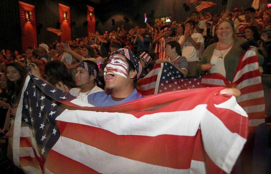 Rudy Rosales waves the U.S. flag as he joins hundreds of other soccer fans to watch the United States team play Belgium in the World Cup match on Tuesday, July 1, 2014 at the Palladium Theaters. The loud and raucous chants and cheers for the team by the supporters were eventually stifled as Belgium managed a 2-1 victory over the United States. Photo: Kin Man Hui, San Antonio Express-News / ©2014 San Antonio Express-News