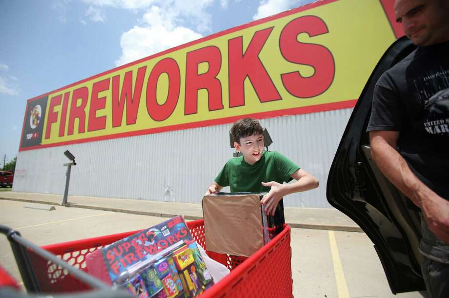 Noah Zakharia, 10, happily helps his father Jack Zakharia are among many shopping at warehouses across the country to get ready for their own celebrations on Independence Day. Photo: Mayra Beltran, Staff / © 2014 Houston Chronicle