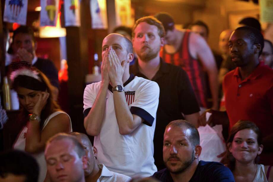Rory Crossin, center, can't hold back his disappointment as the American soccer team is eliminated by Belgium during extra time on July 1 at The Richmond Arms Pub in Houston. Photo: Marie D. De Jesus, Houston Chronicle / © 2014 Houston Chronicle