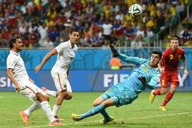US forward Chris Wondolowski (L) shoots past Belgium's goalkeeper Thibaut Courtois during a Round of 16 football match between Belgium and USA at Fonte Nova Arena in Salvador during the 2014 FIFA World Cup on July 1, 2014.      AFP PHOTO/ FRANCISCO LEONGFRANCISCO LEONG/AFP/Getty Images