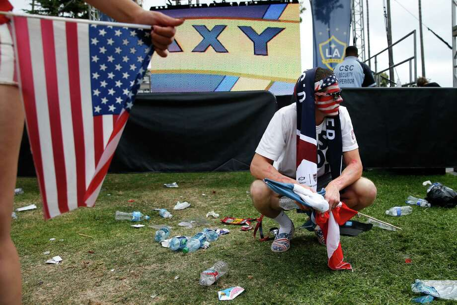 Steve Essex, 26, squats on the lawn after watching the World Cup soccer match between the United States and Belgium at a viewing party on Tuesday, July 1, 2014, in Redondo Beach, Calif. Belgium defeated the USA 2-1 in extra time. (AP Photo/Jae C. Hong) Photo: Jae C. Hong, STF / AP
