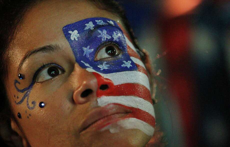 A fan of the U.S. national soccer team, with her face painted with the nation's colors watches her team's World Cup round of 16 match against Belgium on a live telecast inside the FIFA Fan Fest area on Copacabana beach in Rio de Janeiro, Brazil, Tuesday, July 1, 2014. Belgium beat the United States 2-1 in extra time to reach World Cup quarterfinals. (AP Photo/Leo Correa) Photo: Leo Correa, STR / AP