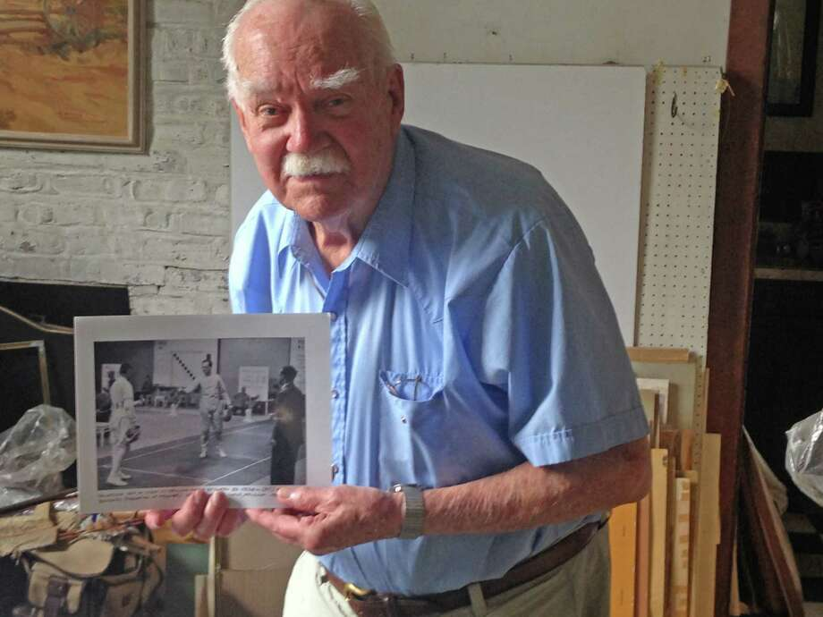 Ed Vebell, 93, holds a photo of himself competing in the 1952 Helsinki Olympics in epee fencing. Vebell, who was recently inducted into the US Fencing Hall of Fame, finished 13th at the event. Photo: Ryan Lacey/Staff Photo / Westport News Contributed