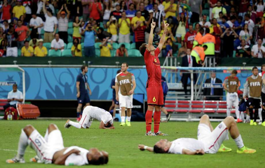Exhausted U.S. players surround Axel Witsel (6), who celebrates Belgium's 2-1 win in extra time Tuesday at the World Cup. The loss in the round of 16 eliminated the U.S. team; Belgium moved to the quarterfinals. Photo: Felipe Dana, STF / AP