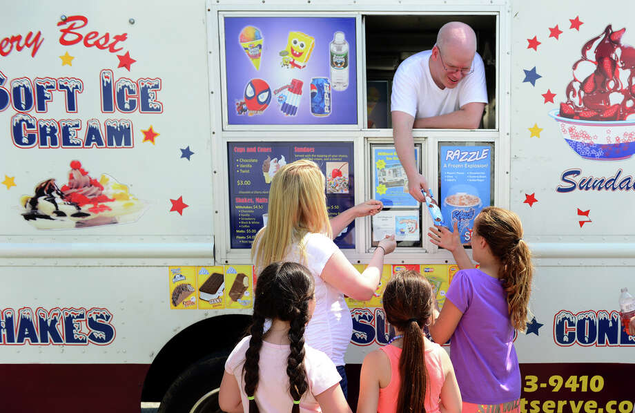 Kids in City of Milford's MCCCI Summer Camp get ice cream from Milford Soft Serve owner Pat Cole at the Westshore Neighborhood Center in Milford, Conn. on Tuesday July 1, 2014. Cole's wife Stefanie, outside of truck at left, is also owner and helped kids with their order and change. Pat and Stefanie at teachers at Fairfield Ludlowe High School and this is their summertime business. Photo: Christian Abraham / Connecticut Post