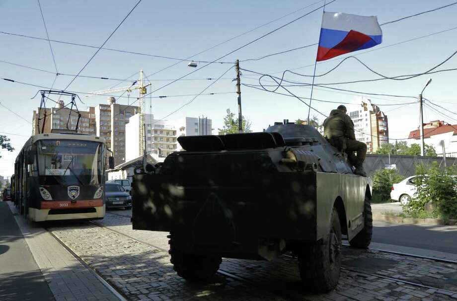A pro-Russian fighters' armored troop carrier guards the roads near the captured Interior Ministry headquarters in Donetsk, eastern Ukraine, on Tuesday. Photo: Dmitry Lovetsky / Associated Press / AP